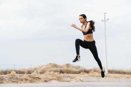 Attractive young fitness girl working out outdoors, jumping