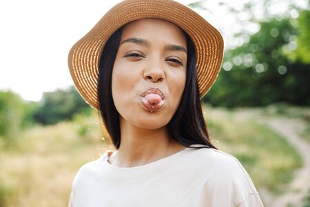 Photo of funny woman wearing straw hat and lip piercing sticking out her tongue at camera while walking in green park 免版税图像