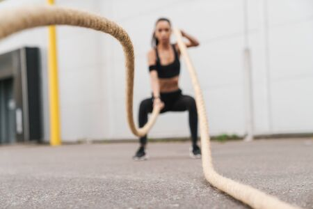 Attractive confident young fitness girl working out outdoors, crossfit exercising