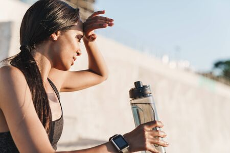 Close up of an attractive fit tired sportswoman outdoors, drinking water from a bottle