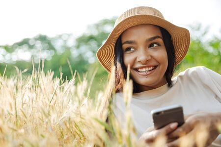 Portrait of happy woman wearing lip piercing and straw hat typing on cellphone while lying on grass in green park