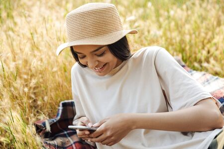 Portrait of pleased woman wearing lip piercing and straw hat typing on cellphone while lying on grass in green park