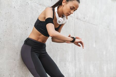 Attractive young fitness girl leaning on a wall while standing outdoors, resting after workout, looking at smart watch