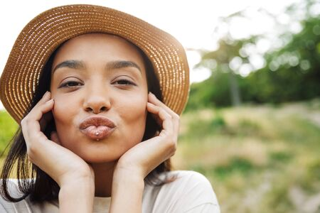 Photo of cute woman wearing straw hat and lip piercing making kiss face at camera while walking in green park