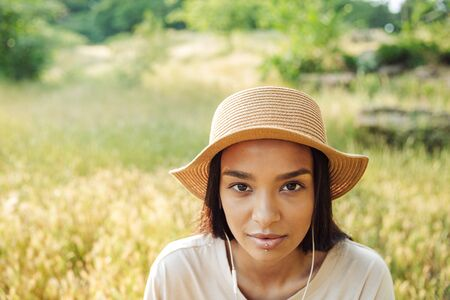 Portrait of beautiful woman wearing lip piercing and straw hat using earphones while sitting on grass in green park