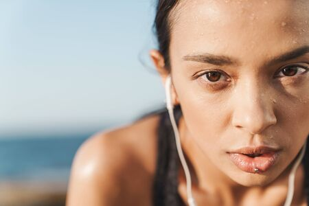 Closeup portrait of beautiful tired young strong sports woman outdoors at the beach at morning have a rest listening music with earphones. Stock fotó