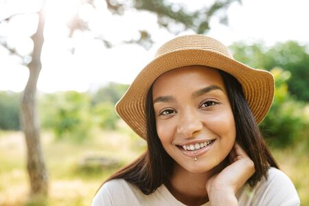 Photo of cheerful woman wearing straw hat and lip piercing smiling at camera while walking in green park