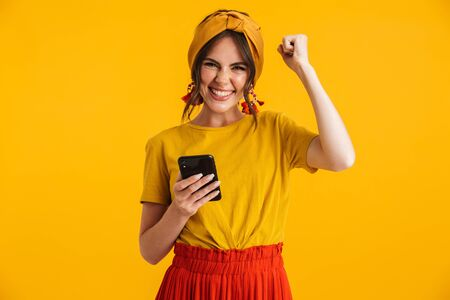 Portrait of a pretty cheerful young girl casually dressed standing isolated over yellow background, holding mobile phone, celebrating success