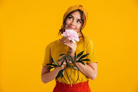 Portrait of a pretty lovely young girl casually dressed standing isolated over yellow background, holding peony flower