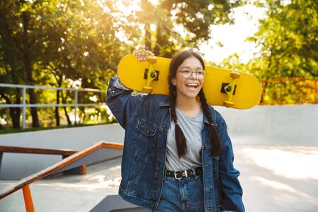 Image of happy girl dressed in denim wear smiling and rejoicing while holding skateboard in skate park
