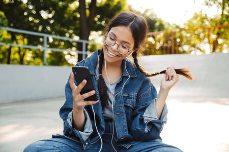Image of young girl dressed in denim wear using smartphone and earphones while sitting on skateboard in skate park