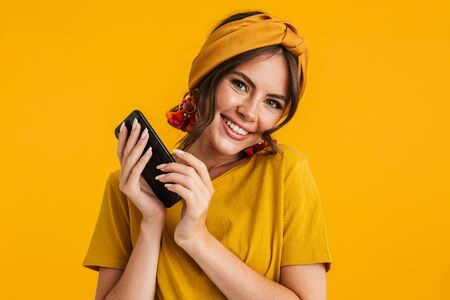 Portrait of a pretty cheerful young girl casually dressed standing isolated over yellow background, holding mobile phone Stock fotó
