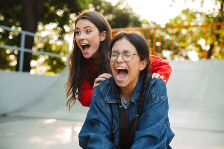 Image of two delighted girls dressed in denim wear screaming and riding skateboard together in skate park