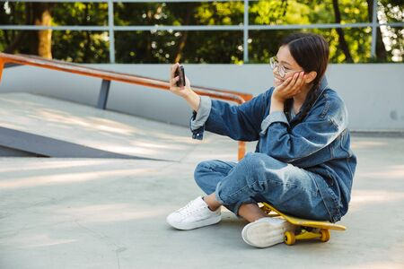 Image of pretty girl dressed in denim wear taking selfie photo on smartphone while sitting on skateboard in skate park Фото со стока