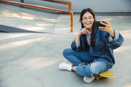 Image of cute girl dressed in denim wear taking selfie photo on smartphone while sitting on skateboard in skate park