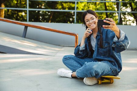 Image of young girl dressed in denim wear taking selfie photo on smartphone while sitting on skateboard in skate park