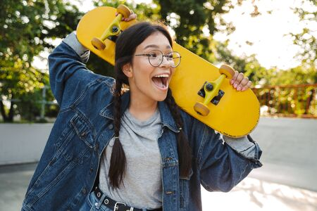 Image of excited girl dressed in denim wear screaming and rejoicing while holding skateboard in skate park Фото со стока