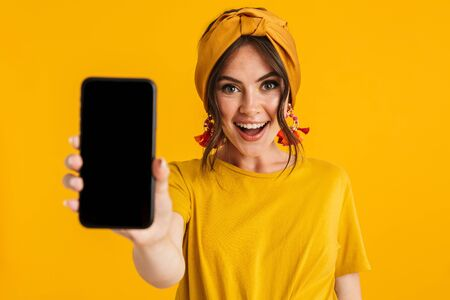 Portrait of a pretty cheerful young girl casually dressed standing isolated over yellow background, showing blank screen mobile phone