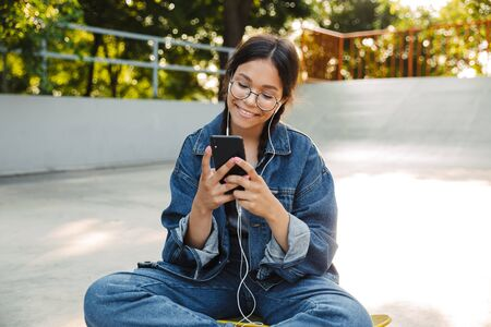 Image of pretty girl dressed in denim wear using smartphone and earphones while sitting on skateboard in skate park Фото со стока