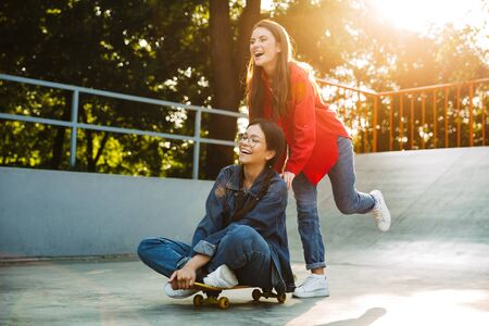 Image of two joyful girls dressed in denim wear laughing and riding skateboard together in skate park