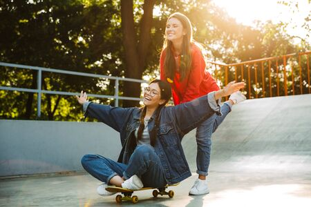 Image of two happy girls dressed in denim wear laughing and riding skateboard together in skate park Фото со стока