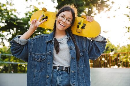 Image of delighted girl dressed in denim wear smiling and showing peace sign while holding skateboard in skate park Фото со стока