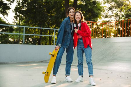 Image of two brunette girls dressed in denim wear laughing and hugging together while holding skateboard in skate park