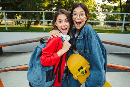 Image of two excited girls dressed in denim wear smiling and hugging together while holding skateboard in skate park