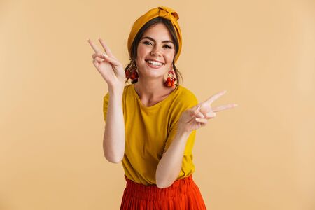 Portrait of a pretty cheerful young girl casually dressed standing isolated over yellow background, showing peace gesture
