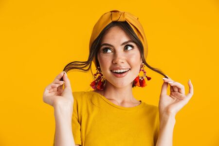 Portrait of a pretty cheerful young girl casually dressed standing isolated over yellow background, playing with her hair Stock fotó