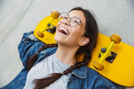 Image of happy girl dressed in denim wear laughing and rejoicing while holding skateboard over concrete wall Фото со стока