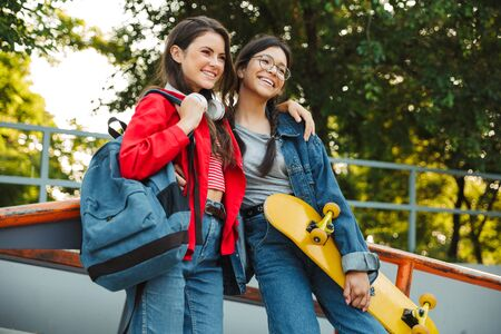 Image of two pleased girls dressed in denim wear smiling and hugging together while holding skateboard in skate park