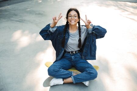 Image of happy girl dressed in denim wear smiling and showing peace sign while sitting on skateboard in skate park