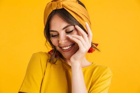 Portrait of a pretty cheerful young girl casually dressed standing isolated over yellow background, posing with hand on her face