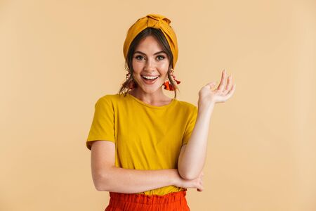 Portrait of a pretty cheerful young girl casually dressed standing isolated over yellow background, posing Stock fotó