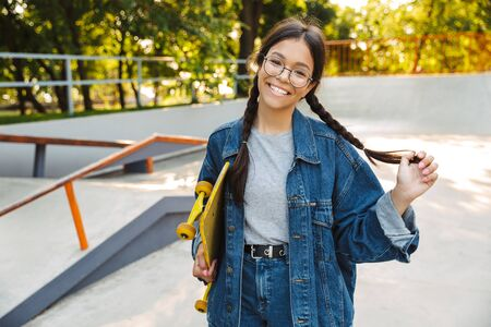 Image of caucasian girl dressed in denim wear smiling and rejoicing while holding skateboard in skate park