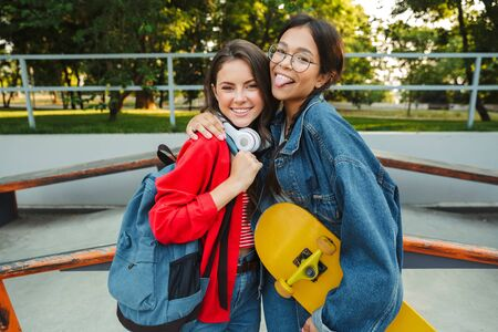 Image of two funny girls dressed in denim wear smiling and hugging together while holding skateboard in skate park