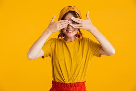 Portrait of a pretty cheerful young girl casually dressed standing isolated over yellow background, cover eyes with hands Stok Fotoğraf