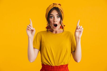 Portrait of a pretty excited young girl casually dressed standing isolated over yellow background, pointing fingers at copy space