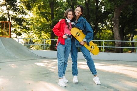 Image of two happy girls dressed in denim wear smiling and hugging together while holding skateboard in skate park