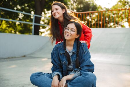 Image of two pretty girls dressed in denim wear laughing and riding skateboard together in skate park Фото со стока