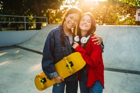 Image of two joyful girls dressed in denim wear smiling and hugging together while holding skateboard in skate park Фото со стока