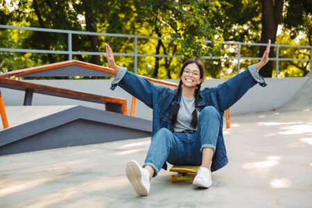 Image of surprised girl dressed in denim wear smiling and rejoicing while riding skateboard in skate park