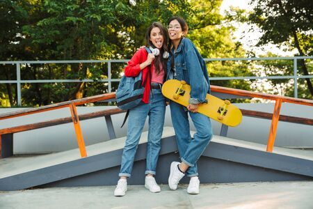 Image of two joyful girls dressed in denim wear sticking out their tongues and hugging while holding skateboard in skate park
