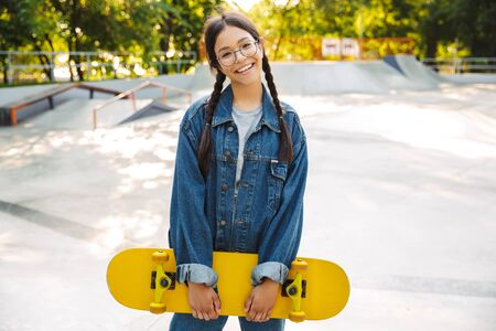 Image of joyful girl dressed in denim wear smiling and rejoicing while holding skateboard in skate park Фото со стока