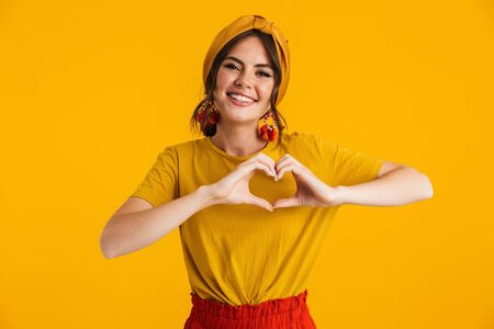 Portrait of a pretty cheerful young girl casually dressed standing isolated over yellow background, showing heart gesture