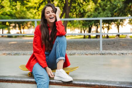 Image of joyous woman dressed in casual wear smiling at camera while sitting on skateboard in park