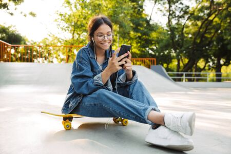 Image of beautiful girl dressed in denim wear using smartphone and earphones while sitting on skateboard in skate park Фото со стока