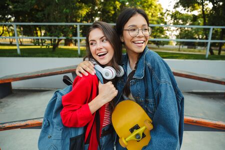 Image of two attractive girls dressed in denim wear smiling and hugging together while holding skateboard in skate park Фото со стока