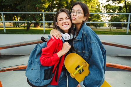 Image of two cute girls dressed in denim wear smiling and hugging together while holding skateboard in skate park